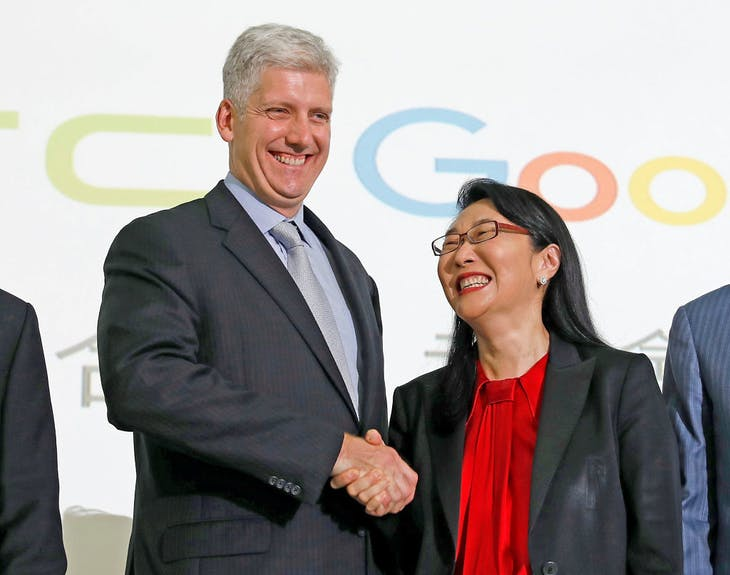 Google hardware executive Rick Osterloh (2n-L) shakes hand with HTC CEO Cher Wang during a news conference to announce Google to acquire HTC's Pixel s...